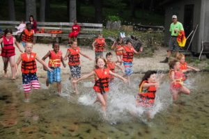 kids in life jackets running into lake