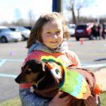 Girl holding dog dressed as turkey